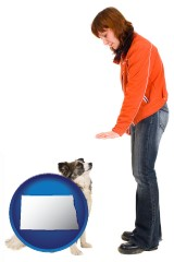 north-dakota map icon and a woman training a pet dog