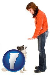 vermont map icon and a woman training a pet dog