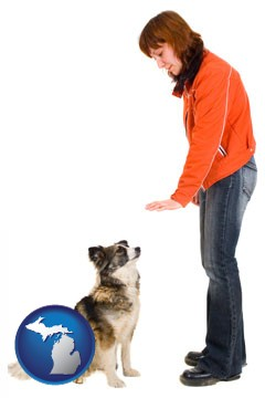 a woman training a pet dog - with Michigan icon